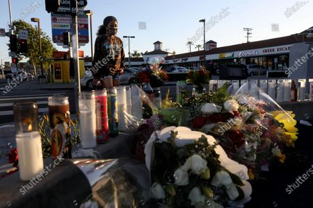 Liliana Ruiz, of Los Angeles, stops at a memorial to pay her respect for Alexis Carbajal, 24, who was shot and killed by Carlos Lopez, 49, who went on a shooting rampage, at the Starbucks near 28th Street and Figueroa, on Wednesday, April 28, 2021 in Los Angeles, CA. Carlos Lopez, 49, went on a shooting rampage in Los Angeles - killing two people and wounding two others - he was fatally shot by police after a standoff on the 91 Freeway in Fullerton. (Gary Coronado / Los Angeles Times)