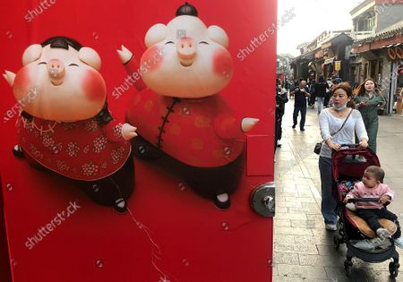 """Chinese visit a popular tourist area known for shopping, cultural gifts and souvenirs in Beijing on Thursday, April 29, 2021.  Expanding domestic consumption is a priority in China's """"dual circulation"""" economic plan first highlighted by President Xi Jinping last month, which also called for a reduced dependence on foreign markets."""