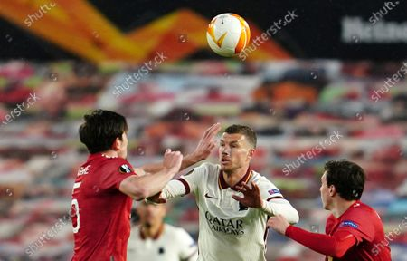 Stock Photo of Roma's Edin Dzeko, center, duels for the ball with Manchester United's Harry Maguire, left, and Manchester United's Victor Lindelof during the Europa League semi final, first leg soccer match between Manchester United and Roma at Old Trafford in Manchester, England