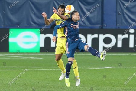 Arsenal's Gabriel Martinelli, right, jumps for a header with Villareal's Raul Albiol during the Europa League semifinal first leg soccer match between Villarreal and Arsenal at the Estadio de la Ceramica stadium in Villarreal, Spain
