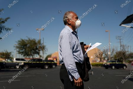"""Stock Picture of Hilario Hernandez waits to receive a dose of the Moderna COVID-19 vaccine at a mobile clinic set up in the parking lot of a shopping center in Orange, Calif., . The mobile unit, launched in February by Families Together of Orange County, began its service to provide better access to the COVID-19 vaccine within the community and to prevent vaccine hesitation, according to mobile operations manager Parsia Jahanbani. """"There's a lot of people that are hesitant to go to vaccine centers to get vaccinated for various reasons. They might be afraid of not having paperwork. They might be afraid of not being able to take time off from work,"""" said Jahanbani"""