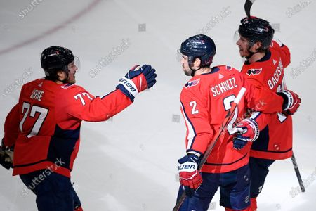 Washington Capitals right wing T.J. Oshie (77) celebrates his goal with defenseman Justin Schultz (2) and center Nicklas Backstrom (19) during the first period of an NHL hockey gameagainst the Pittsburgh Penguins, in Washington