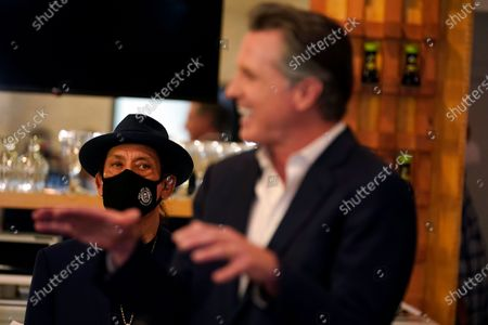 Actor Danny Trejo, left, listens to California Gov. Gavin Newsom at Hanzo Sushi, in San Fernando, Calif. California will extend more than $6 billion in tax breaks to small businesses that received federal aid to weather the economic downturn during the COVID-19 pandemic. Newsom signed a bill Thursday that allows business to write off expenses on their state taxes if they were paid for with Paycheck Protection Program loans