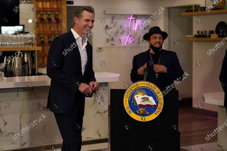 California Gov. Gavin Newsom, left, smiles as he walks up to the podium, past actor Danny Trejo, right, after signing a COVID-19 relief bill for businesses at Hanzo Sushi, in San Fernando, Calif. California will extend more than $6 billion in tax breaks to small businesses that received federal aid to weather the economic downturn during the COVID-19 pandemic. Newsom signed a bill Thursday that allows business to write off expenses on their state taxes if they were paid for with Paycheck Protection Program loans