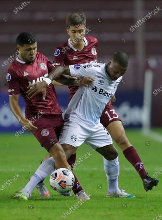 Pedro Geromel of Brazil's Gremio, center fights for the ball with Facundo Perez, left, and Julian Aude of Argentina's Lanus during a Copa Libertadores soccer match, at Néstor Díaz Pérez stadium in Buenos Aires, Argentina