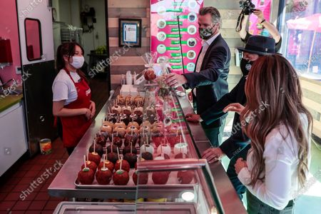California Gov. Gavin Newsom and actor Danny Trejo visit Manzanitas Las Originales gourmet caramel apple shop in San Fernando, Calif. before signing legislation at a news conference