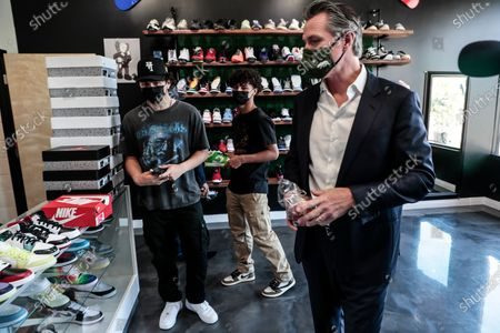 California Gov. Gavin Newsom meets Mario Rodriguez and Rudy Perez of Hype Beast Kicks shoe store while touring downtown. in San Fernando, Calif. before signing legislation at a news conference