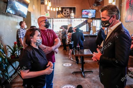Chris and Magaly Colelli, owners of Magaly's restaurant talk with Governor Gavin Newsom in San Fernando, Calif