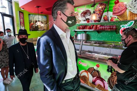 California Gov. Gavin Newsom and actor Danny Trejo visit Manzanitas Las Originales gourmet caramel apple shop downtown before signing legislation at a news conference in San Fernando, Calif