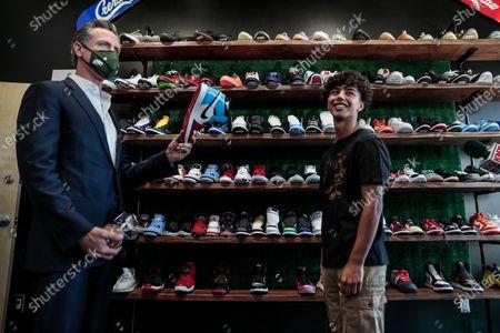 California Gov. Gavin Newsom meets Mario Rodriguez of Hype Beast Kicks shoe store while touring downtown San Fernando, Calif