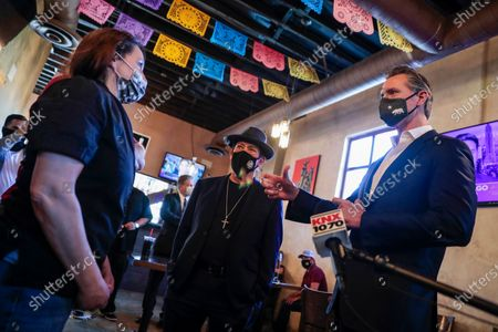 Magaly Colelli owner of Magaly's restaurant talks with Gov. Gavin Newsom and actors Danny Trejo in San Fernando, Calif