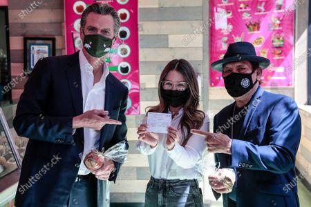 California Gov Gavin Newsom and actor Danny Trejo pose with Sandy Silva, owner of Manzanitas Las Originales gourmet caramel apple shop as she shows off a vaccination card she received today in San Fernando, Calif