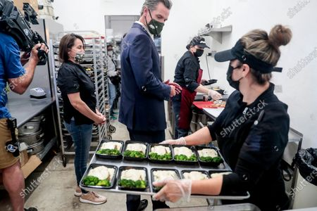 Elva Quinonez prepares food as Governor Gavin Newsom talks with Magaly Colelli at Magaly's restaurant in San Fernando, Calif