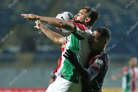 Juan Sanchez (L) of Palestino in action against Eder Ferreira (R) of Atletico Goianiense during the Copa Sudamericana soccer match between Palestino and Atletico Goianiense at El Teniente Stadium in Rancagua, Chile, 29 April 2021.