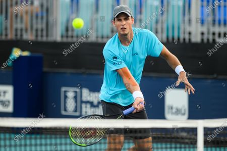 Stock Photo of Vasek Pospisil of Canada hits a forehand during his loss to Mackenzie McDonald of the United States in the first round at the Miami Open on , on the grounds of Hard Rock Stadium in Miami Gardens, Florida