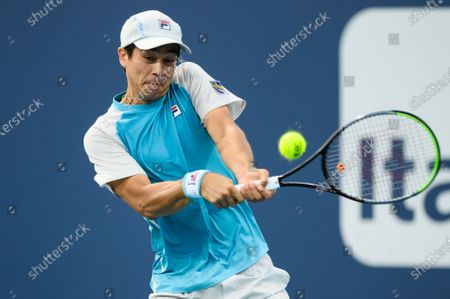 Mackenzie McDonald of the United States hits a backhand during his victory over Vasek Pospisil of Canada in the first round at the Miami Open on , on the grounds of Hard Rock Stadium in Miami Gardens, Florida