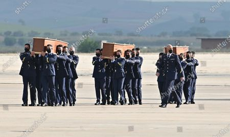 Members of the army carry the coffins of slain Spanish journalists David Beriain Amatriain and Roberto Fraile, and president of the anti-poaching group Chengeta Wildlife, Irish Rory Young, as they arrive at the Torrejon de Ardoz military airport in Madrid, Spain, 30 April 2021. They were killed on 27 April in Burkina Faso while working on a documentary about poaching in the Pama area of the country.