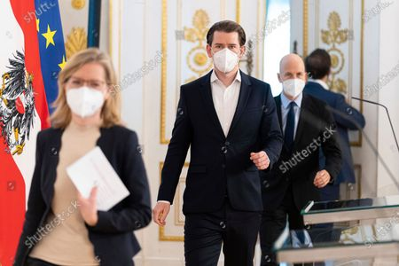 Austria's minister for climate protection, technology and innovation Leonore Gewessler, Austrian Chancellor Sebastian Kurz and Austria's Minister for employment Martin Kocher, from left, arrive at a press conference, wearing face masks, at the federal chancellery in Vienna, Austria, . The Austrian government informs about the government's 'Sprungbrett' program for the long-term unemployed and job opportunities through the creation of 'green jobs