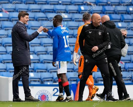 Rangers Manager Steven Gerrard bumps fists with Glen Kamara of Rangers at the final whistle after a 4-1 victory, with Rangers Assistant Manager Gary McAllister, right