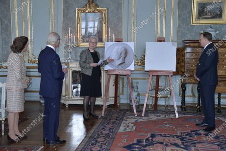 Queen Silvia of Sweden (L) looks on as King Carl XVI Gustaf of Sweden (2-L) receives a gift from the First Vice Chairman of the Parliament, Asa Lindestam and Prime Minister Stefan Lofven (R) on his 75th birthday at the Royal Palace in Stockholm, Sweden, 30 April 2021. The gift, a placard of plaster of the king, will be hung in the Swedish Parliament.