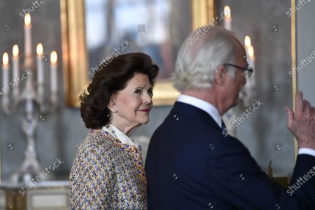 Queen Silvia of Sweden looks on as King Carl Gustaf of Sweden receives a gift on his 75th birthday at The Royal Palace in Stockholm, Sweden
