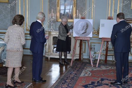 Stock Image of Queen Silvia of Sweden looks on as King Carl Gustaf of Sweden receives a gift from the First Vice Chairman of the Parliament, Åsa Lindestam and Prime Minister Stefan Löfven on his 75th birthday at The Royal Palace in Stockholm, Sweden on Friday, April 30, 2021. The gift, a plaster plaque of the king, will be hung in the Swedish Parliament.