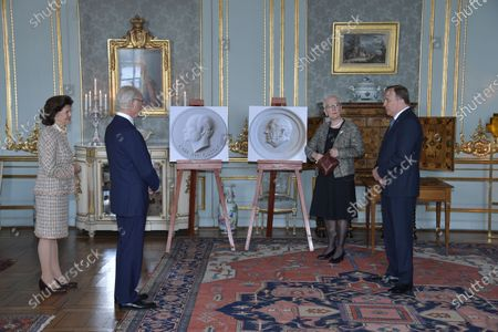 Stock Photo of Queen Silvia of Sweden looks on as King Carl Gustaf of Sweden receives a gift from the First Vice Chairman of the Parliament, Åsa Lindestam and Prime Minister Stefan Löfven on his 75th birthday at The Royal Palace in Stockholm, Sweden on Friday, April 30, 2021. The gift, a plaster plaque of the king, will be hung in the Swedish Parliament.