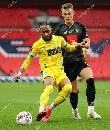 Will Smith of Harrogate Town and Lamar Reynolds of Concord Rangers compete for the ball