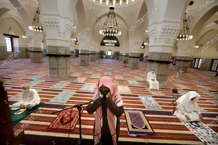 Saudi cleric Mohammed Al Hajj recites the call to prayers as worshippers wearing face masks and observing social distancing guidelines to protect against the new coronavirus, attend prayers at Al- Jaffali mosque ahead of Friday prayer during the Muslim fasting month of Ramadan, in Jiddah, Saudi Arabia