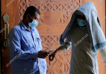 Muslim worshipper covered by his prayer carpet and wearing a mask to curb the spread of the coronavirus has her temperature measured as he enters Al- Jaffali mosque ahead of Friday prayer during the Muslim fasting month of Ramadan, in Jiddah, Saudi Arabia
