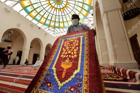 Worker collects carpets, which were used as a marker to help practice social distancing to curb the spread of the coronavirus, at Al- Jaffali mosque after Friday prayers during the Muslim fasting month of Ramadan, in Jiddah, Saudi Arabia