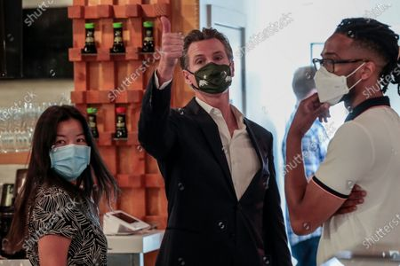 San Fernando, CA, Thursday, April 29, 2021 - California Governor Gavin Newsom waves goodbye to friends after attending a press conference where he signed legislation that will provide a $6.2 billion tax cut to the hardest hit small businesses in the state at Hanzo Sushi restaurant downtown. (Robert Gauthier/Los Angeles Times)