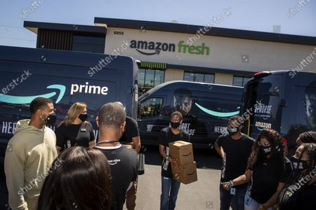 """Amazon Fresh store associates and nonprofit partner Village for Vets are surprised by actor Michael B. Jordan, far left in kahki, who stopped by in promotion of the launch of """"Tom Clancy's Without Remorse,"""" on Prime Video, helping load care packages of food and household items at the Ladera Heights neighborhood store in Los Angeles, CA, Thursday, April 29, 2021. The program reaches over 600 veterans across Los Angeles. The film is available on Amazon's Prime Video April 30, 2021. (Jay L. Clendenin / Los Angeles Times)"""