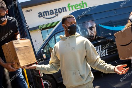 """In promotion of the launch of """"Tom Clancy's Without Remorse,"""" on Prime Video, actor and star of the film, Michael B. Jordan helped load vans with his face on them, as he joined Amazon Fresh store associates and nonprofit partner Village for Vets in loading care packages of food and household items at the Ladera Heights neighborhood store in Los Angeles, CA, Thursday, April 29, 2021. The program reaches over 600 veterans across Los Angeles. The film is available on Amazon's Prime Video April 30, 2021. (Jay L. Clendenin / Los Angeles Times)"""