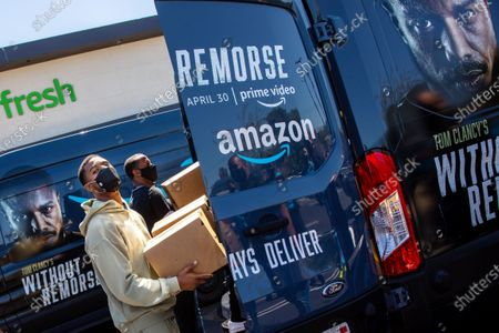 """In promotion of the launch of """"Tom Clancy's Without Remorse,"""" on Prime Video, actor and star of the film, Michael B. Jordan is seen loading a van with his face on it, as he joined Amazon Fresh store associates and nonprofit partner Village for Vets in loading care packages of food and household items at the Ladera Heights neighborhood store in Los Angeles, CA, Thursday, April 29, 2021. The program reaches over 600 veterans across Los Angeles. The film is available on Amazon's Prime Video April 30, 2021. (Jay L. Clendenin / Los Angeles Times)"""
