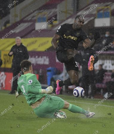 Michail Antonio of West Ham United takes evasive action from the sliding Nick Pope of Burnley