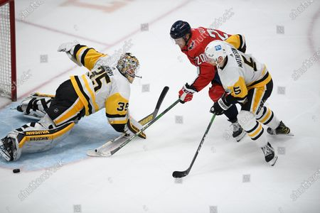 Washington Capitals center Lars Eller (20) battles for the puck against Pittsburgh Penguins goaltender Tristan Jarry (35) and Pittsburgh Penguins defenseman Mike Matheson (5) during the first period of an NHL hockey game, in Washington