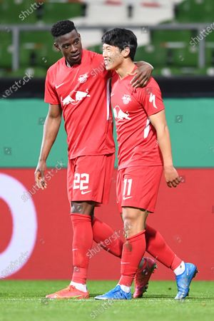 Stock Image of Leipzig's Hwang Hee-chan, right, celebrates with Leipzig's Nordi Mukiele after scoring his side's opening goal during the German soccer cup semifinal soccer match between Werder Bremen and RB Leipzig at the Weserstadion stadium in Bremen, Germany