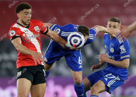 Southampton's Che Adams, left, and Leicester's Jonny Evans, centre, challenge for the ball during the English Premier League soccer match between Southampton and Leicester City at St. Mary's Stadium in Southampton, England