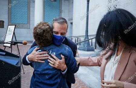 Los Angeles Mayor Eric Garcetti hugs Patti Giggans, Denim Day founder and CEO of Peace Over Violence and LA City Council President Nury Martinez as local leaders wearing their jeans in solidarity with survivors of rape and sexual assault, gathered at Los Angeles City Hall to proclaim April 28th Denim Day in Los Angeles which was started by Giggans in 1999. The annual Denim Day education campaign began 22 years ago in Los Angeles. Now a worldwide movement, Denim Day invites people everywhere to wear their jeans in solidarity with survivors, and reminds everyone that there is no excuse and never an invitation to rape. The annual observance recalls an Italian Supreme Court case that sparked international outrage when a judge overturned a lower court's conviction of a rapist because the victim wore jeans. The judges ruled that because the victim was wearing tight jeans, she must have helped her attacker remove them, thus implying consent. Los Angeles City Hall on Wednesday, April 28, 2021 in Los Angeles, CA. (Al Seib / Los Angeles Times).