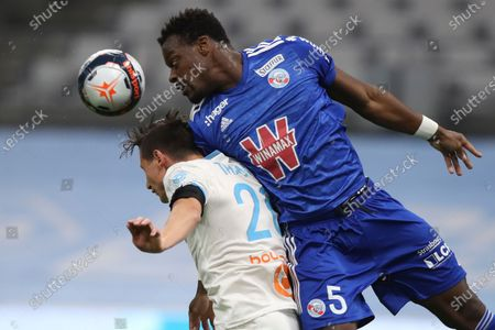 Marseille's Florian Thauvin, left, jumps for a header with Strasbourg's Lamine Kone during the French League One soccer match between Marseille and Strasbourg at the Stade Veledrome stadium in Marseille, France