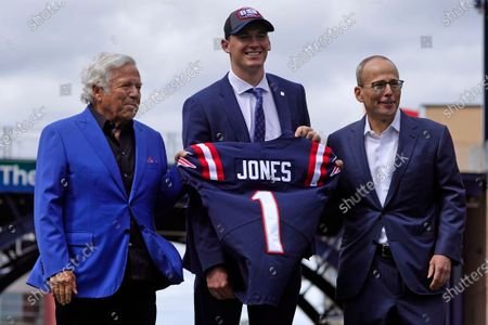 New England Patriots 2021 first-round draft pick, former Alabama quarterback Mac Jones, center, poses with team owner Robert Kraft, left, and team president Jonathan Kraft, in Foxborough, Mass. The Patriots selected Jones with the 15th pick in Thursday's NFL Draft