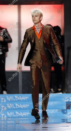 Singer Machine Gun Kelly walks onto the stage to speak during second round of the 2021 NFL Draft in Cleveland, Ohio on Friday, April 30, 2021.