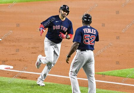 Stock Image of Boston Red Sox left fielder J.D. Martinez #28 rounds third base and slaps hands with Boston Red Sox third base coach Carlos Febles #52 after Martinez hits a 3 run home run in the top of the first inning during an MLB game between the Boston Red Sox and the Texas Rangers at Globe Life Field in Arlington, TX Albert Pena/CSM