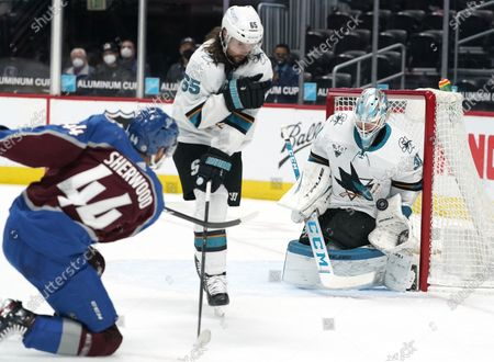 Stock Image of San Jose Sharks goaltender Martin Jones, right, makes a glove-save of a shot that passed by defenseman Erik Karlsson off the stick of Colorado Avalanche left wing Kiefer Sherwood in the second period of an NHL hockey game, in Denver