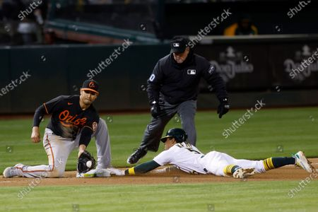 Oakland Athletics Tony Kemp (R) slides safely into third base beating the tag by Baltimore Orioles third baseman Rio Ruiz (L) as third base umpire Rob Drake (C) watches during the ninth inning of the MLB baseball game between the Baltimore Orioles and the Oakland Athletics at RingCentral Coliseum in Oakland, California, USA, 30 April 2021.