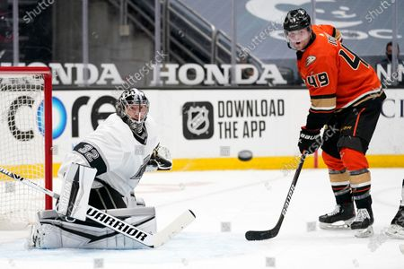 Los Angeles Kings goaltender Jonathan Quick, left, watches a shot come in along with Anaheim Ducks left wing Max Jones during the second period of an NHL hockey game, in Anaheim, Calif