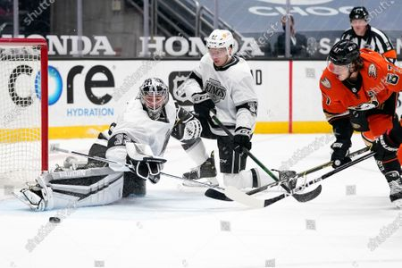 Los Angeles Kings goaltender Jonathan Quick, left, deflects a shot by Anaheim Ducks center Rickard Rakell, right, as defenseman Tobias Bjornfot defends during the second period of an NHL hockey game, in Anaheim, Calif