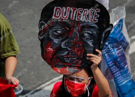 Stock Picture of A demonstrator carries a placard with the image of Philippine President Rodrigo Duterte during a protest to mark Labor Day in Quezon City, Metro Manila, Philippines, 01 May 2021. Various cause-oriented groups pushing for labor rights protested in Manila with calls for an increase in financial assistance due to COVID-19 and mass testing among others.