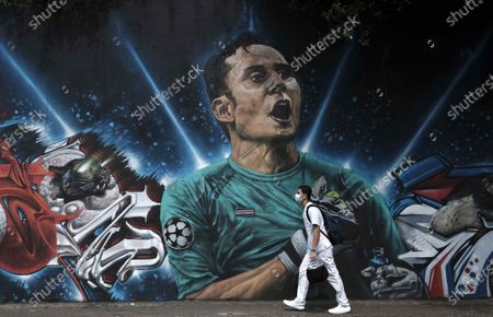 A nurse wearing a mask passes in front of a mural with the image of Costa Rican goalkeeper Keylor Navas, in the city of San Jose, Costa Rica, 30 April 2021. Accelerating vaccination and decreasing the third wave of COVID-19 infections are the most urgent needs in Costa Rica, a country on the verge of hospital collapse, the College of Doctors and Surgeons told EFE news agency this Friday.